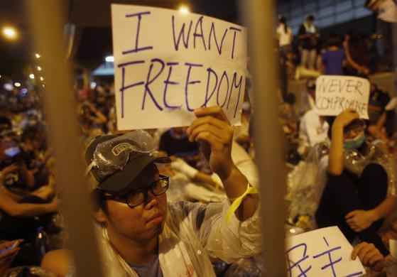 Protesters hold up signs during an evening rally attended by thousands in front of the government headquarters in Hong Kong