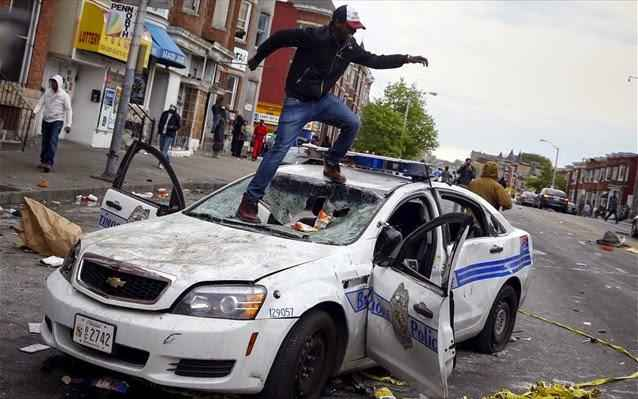 demonstrators-jump-on-a-damaged-baltimore-police-department-vehicle-during-clashes-in-baltimore