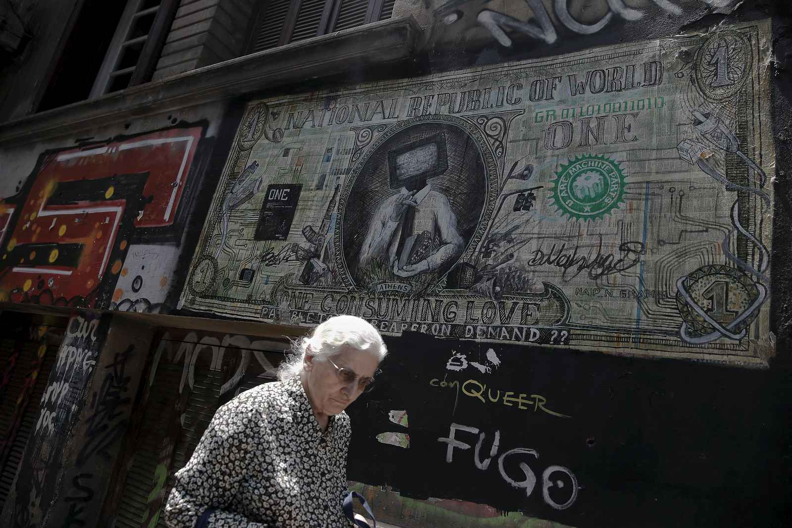 "A woman walks past graffiti illustrating a modified dollar banknote in Athens June 3, 2015. Greek Prime Minister Alexis Tsipras on Wednesday called on international creditors to show ""realism"" and help clinch a deal that will end speculation of the country leaving the euro zone.  REUTERS/Alkis Konstantinidis"