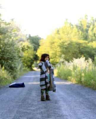 An Afghan girl stands on a road after crossing the Hungarian-Serbian border illegally near the village of Asotthalom, Hungary, June 18, 2015. Hungary says almost 60,000 migrants have entered the country illegally so far this year, and on Wednesday announced it would throw up a 4-metre high fence along its 175-km (110 miles) border with non-European Union member Serbia. Migration experts warn the move risks creating a dangerous logjam in Serbia, an impoverished ex-Yugoslav republic woefully ill-equipped to deal with the influx. REUTERS/Bernadett Szabo