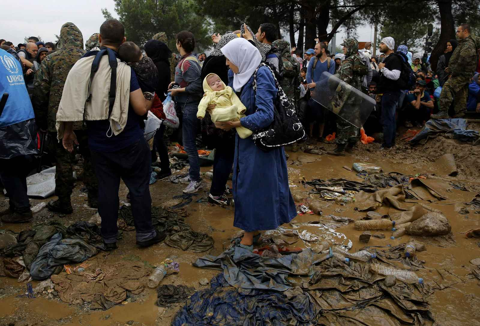 A Syrian refugee carries her baby as she walks through the mud to cross the border from Greece into Macedonia during a rainstorm, near the Greek village of Idomeni, September 10, 2015. Most of the people flooding into Europe are refes fleeing violence and persecution in their home countries who have a legal right to seek asylum, the United Nations said on Tuesday. REUTERS/Yannis Behrakis