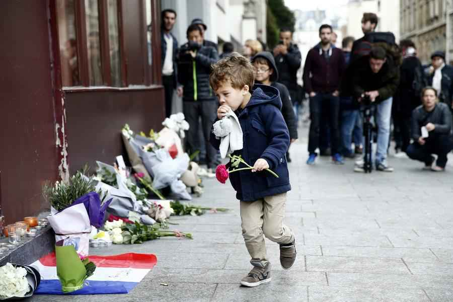 epa05024457 A little boy places a flower in front of the Carillon cafe in Paris, France, 14 November 2015. At least 120 people have been killed in a series of attacks in Paris on 13 November, according to French officials. Eight assailants were killed, seven when they detonated their explosive belts, and one when he was shot by officers, police said. French President Francois Hollande says that the attacks in Paris were an 'act of war' carried out by the Islamic State extremist group. EPA/YOAN VALAT