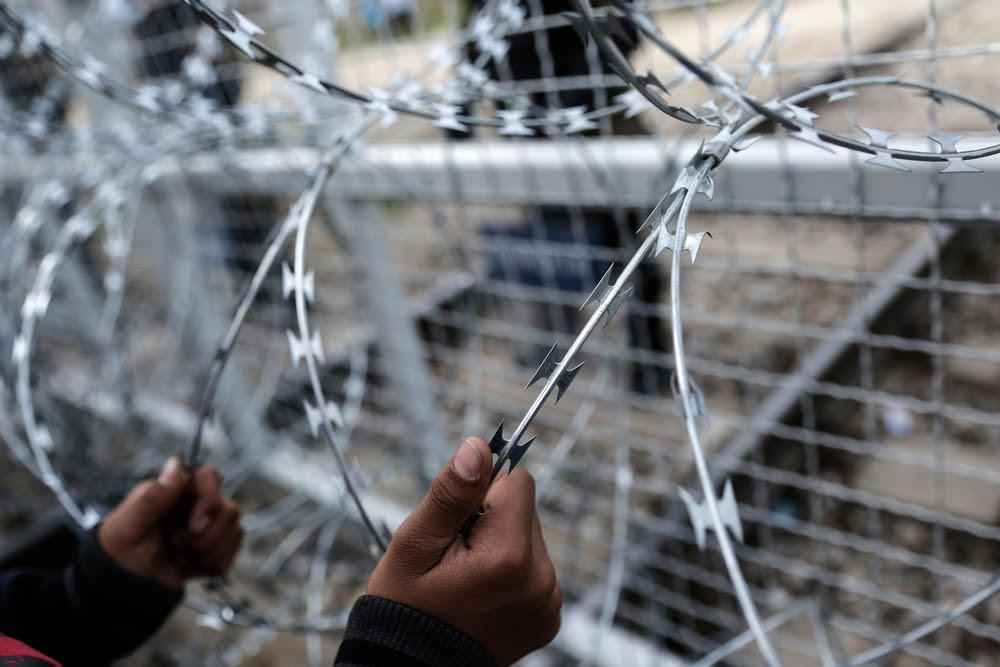An Afghan child holds the fence during protest at the Greek-Macedonian (FYROM) border near the northern Greek village of Idomeni.