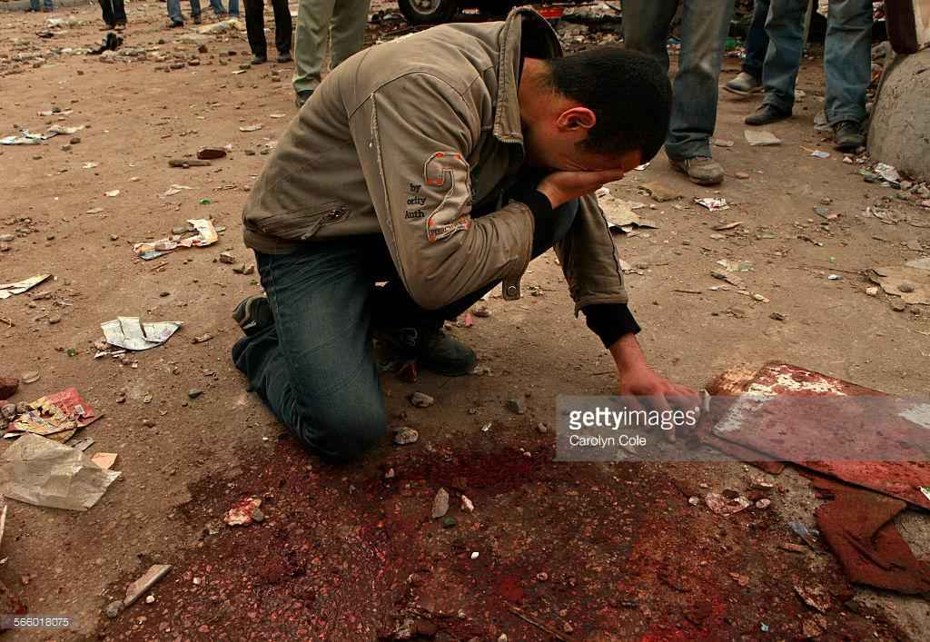 Cole, Carolyn –– – CARIO, EGYPT––FEBRUARY 2, 2011––A protester (anti–Mubarak) mourns the death of his brother at a site on the front line where a pool of blood remains. (Carolyn Cole/Los Angeles Times)