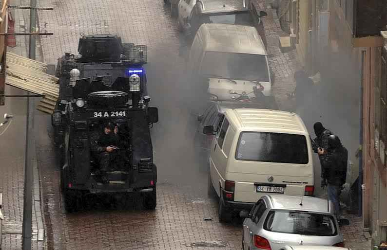 Security forces fire during an operation against two attackers, in Istanbul, Thursday, March 3, 2016. Police in Istanbul on Thursday shot and killed two women who had hidden inside a building after attacking police with gunfire and a hand grenade, an official said. (AP Photo/Emrah Gurel)