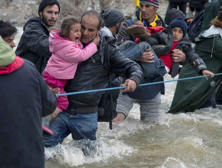 A child cries as migrants cross a river, north of Idomeni, Greece, attempting to reach Macedonia on a route that would bypass the border fence, Monday, March 14, 2016. Hundreds of migrants and refugees walked out of an overcrowded camp on the Greek-Macedonian border Monday, determined to use a dangerous crossing to head north. (AP Photo/Vadim Ghirda)