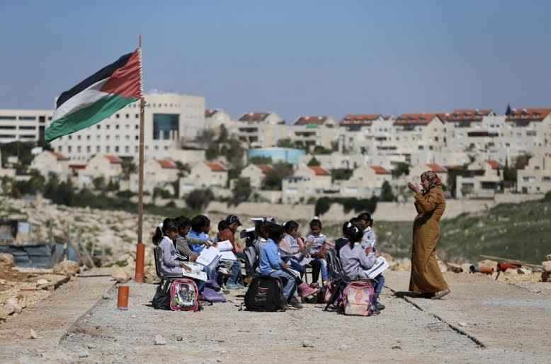 A teacher gives a class to Palestinian bedouin students outdoors near the Jewish settlement of Maale Adumim (seen in the background), in the West Bank village of Al-Eizariya, east of Jerusalem March 1, 2016. The Israeli forces dismantled the caravans that were used as classrooms for the Beduin community school on February 20, residents said. According to school officials, the Israeli army informed them that the containers were removed because they did not have an Israeli-issued construction permit to stay in the area. REUTERS/Ammar Awad TPX IMAGES OF THE DAY - RTS8RKX