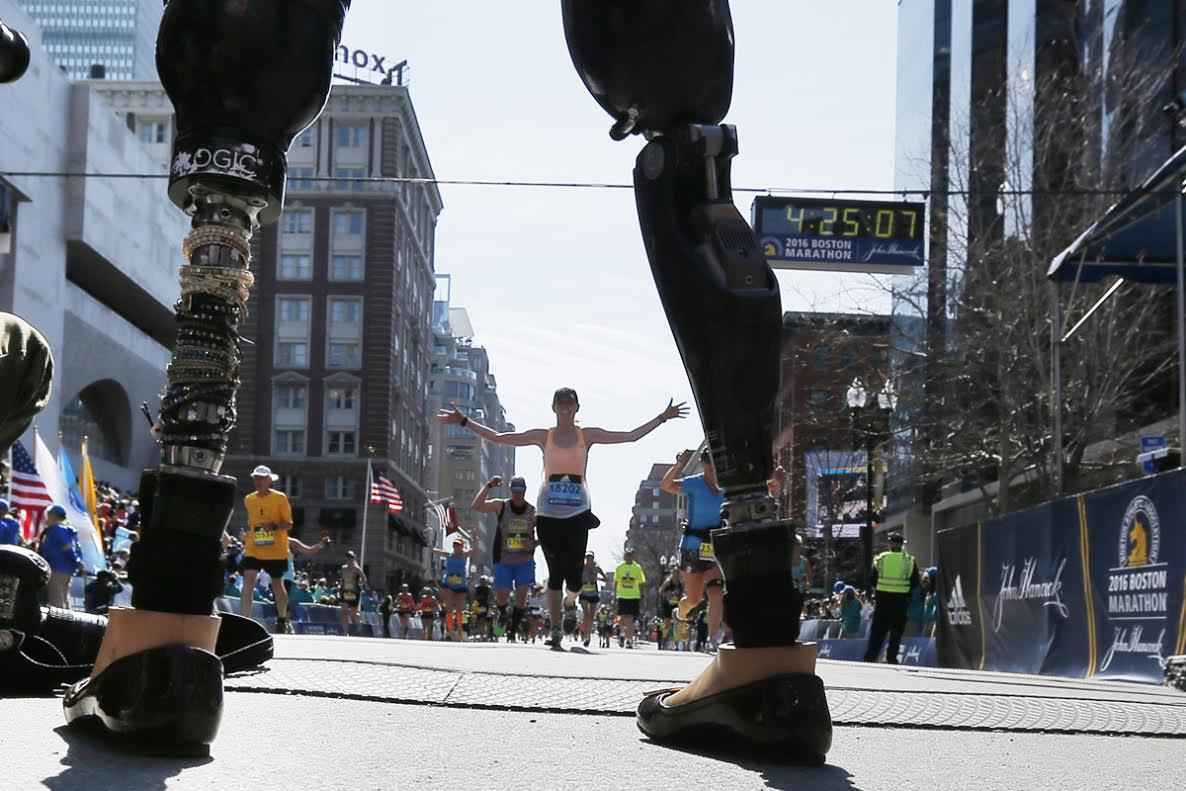 Celeste Corcoran, who lost both her legs in the Boston Marathon bombings, greets runners at they finish the120th running of the Boston Marathon in Boston, Massachusetts April 18, 2016.  REUTERS/Brian Snyder TPX IMAGES OF THE DAY - RTX2AK1W