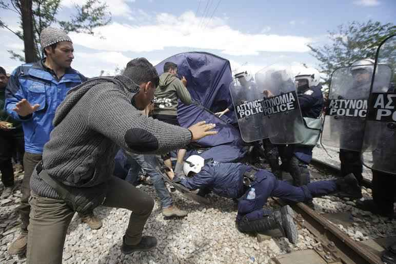 Migrants and refugees scuffle with Greek policemen during a protest at the northern Greek border point of Idomeni, Greece, Thursday, May 5, 2016. Migrants and refigees protested against the poor camp conditions and the closed border. (AP Photo/Gregorio Borgia)