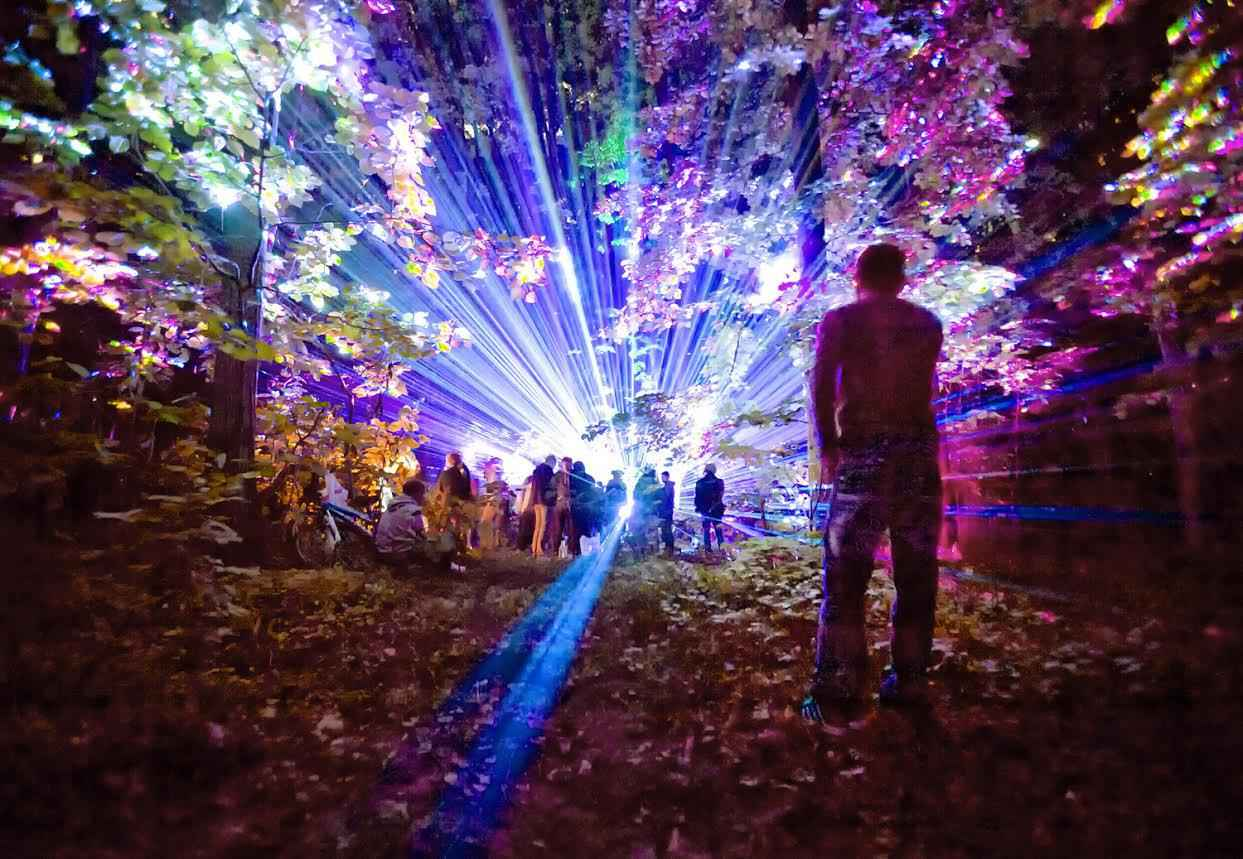 A man watches from a distance as youngsters dance during a music and laser show, in a forest outside Bucharest, Romania, early Saturday, May 21, 2016. People attended in large numbers a display of laser lighting and music that lasted until the morning hours. (AP Photo/Vadim Ghirda)