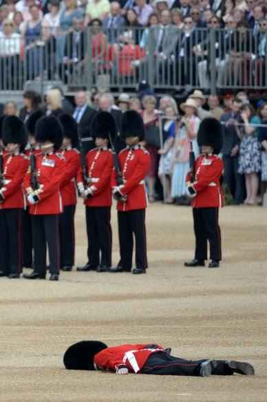 A soldier collapses on Horse Guards Parade ahead of the Queen's Birthday Parade, 'Trooping the Colour', in London on June 11, 2016.  Trooping The Colour and the fly-past are part of a weekend of events to celebrate the Queen's 90th birthday. / AFP PHOTO / OLI SCARFFOLI SCARFF/AFP/Getty Images