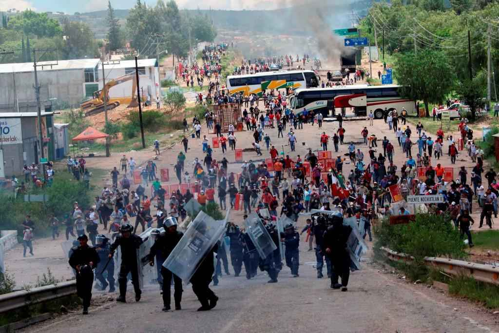 Riot police are forced to fall back as they battle with protesting teachers who were blocking a federal highway in the state of Oaxaca, near the town of Nochixtlan, Mexico, Sunday, June 19, 2016. The teachers are protesting against plans to overhaul the country's education system which include federally mandated teacher evaluations.(AP Photo/Luis Alberto Cruz Hernandez)