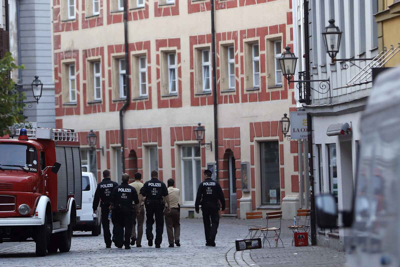 Police officers patrol through the old part of Ansbach, Germany, Monday, July 25, 2016. Bavaria's top security official says a man who blew himself up after being turned away from an open-air music festival in the southern German city was a 27-year-old Syrian who had been denied asylum. (AP Photo/Matthias Schrader)