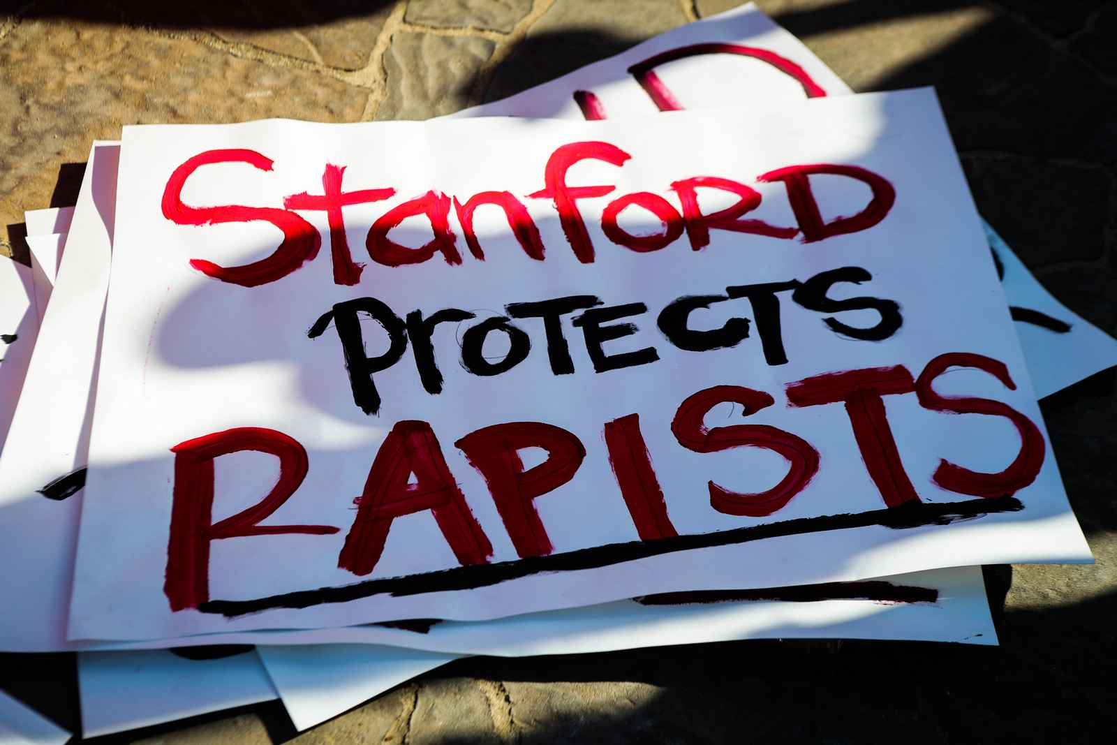 Signs against protectin rapist are seen during the commencement ceremony at Stanford University, in Palo Alto, California, on June 12, 2016. Stanford students are protesting the universitys handling of rape cases alledging that the campus keeps secret the names of students found to be responsible for sexual assault and misconduct. / AFP / GABRIELLE LURIE (Photo credit should read GABRIELLE LURIE/AFP/Getty Images)