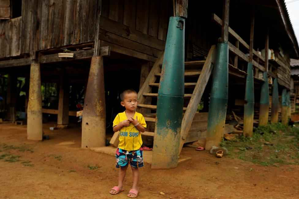A boy stands in front of a house built on bombs dropped by the U.S. Air Force planes during the Vietnam War, in the village of Ban Napia in Xieng Khouang province, Laos September 3, 2016. From 1964 to 1973, U.S. warplanes dropped more than 270 million cluster munitions on Laos, one-third of which did not explode, according to the Lao National Regulatory Authority for UXO (NRA). The bombings were part of a CIA-run, secret operation aimed at destroying the North Vietnamese supply routes along the Ho Chi Minh trail and wiping out its communist allies. They also left a trail of devastation in Laos, which U.S. planes used as a dumping ground for bombs when their original target was unavailable and planes couldn't land with explosives.   REUTERS/Jorge Silva