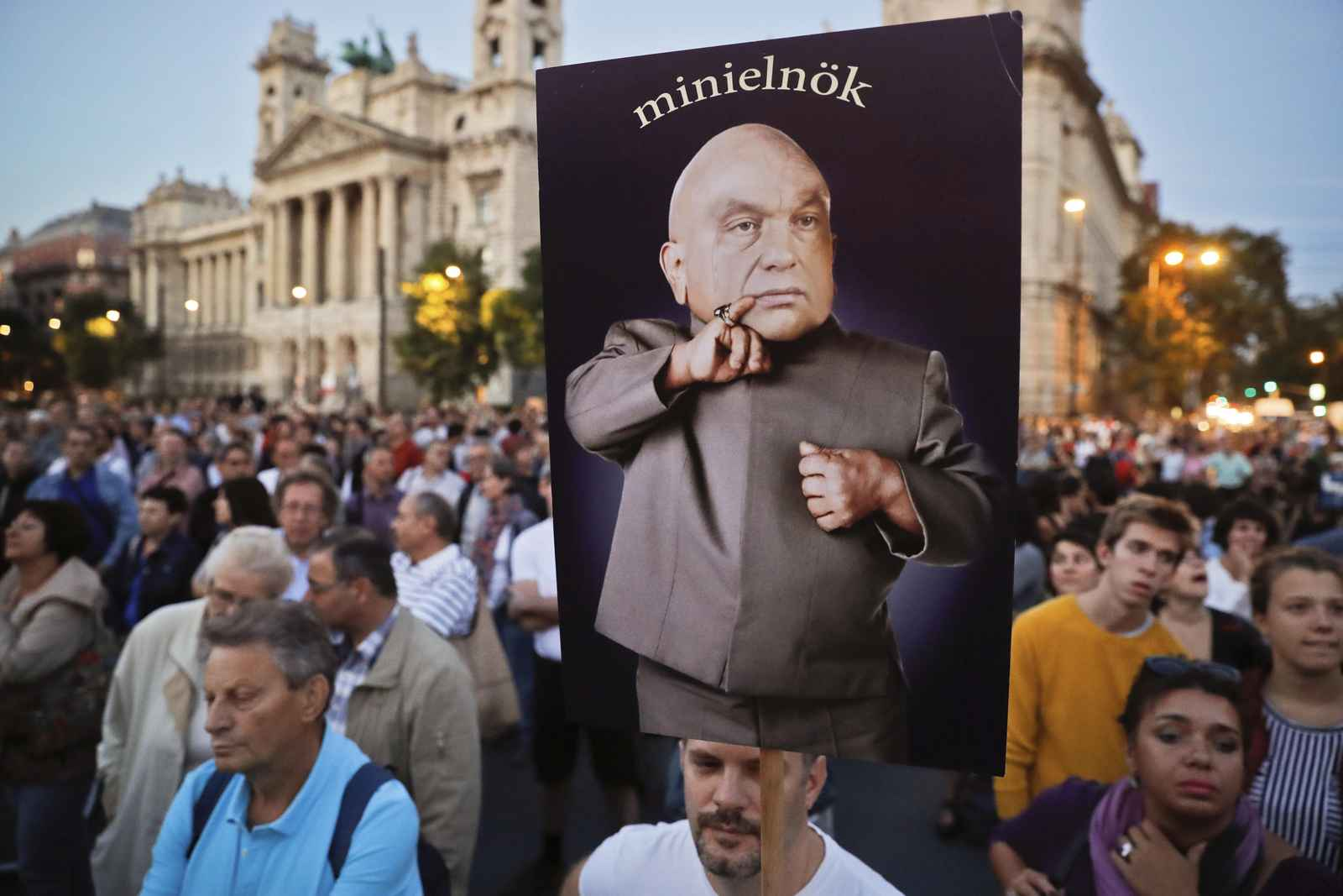 """A man holds a banner depicting Hungarian Premier Viktor Orban, the reads """"mini-prime minister"""" during a protest against Orban's policies regarding migrants in Budapest, Hungary, Friday, Sept. 30, 2016. Hungarians will vote Sunday in a referendum which Prime Minister Viktor Orban hopes will give his government the popular support it seeks to oppose any future plans by the European Union to resettle asylum seekers among its member states.(AP Photo/Vadim Ghirda)"""