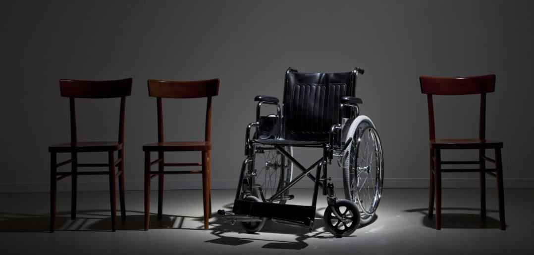 Wheelchair in line of wooden chairs