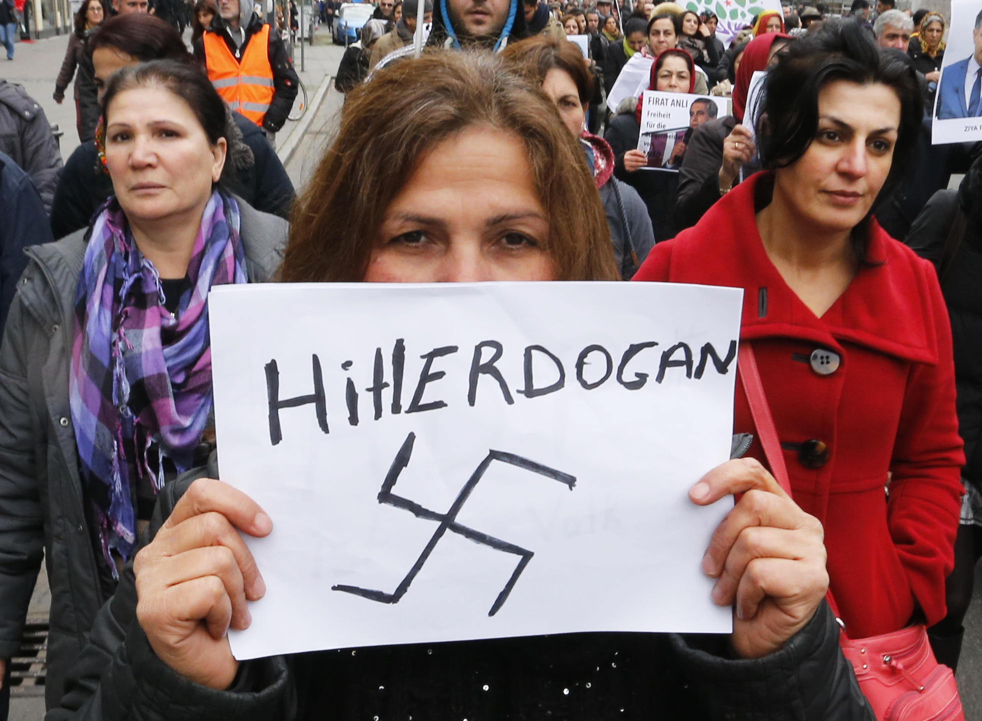 "A Kurdish woman carries a sign with a swastika reading ""Hitlerdogan"" as some hundred Kurds protest against Turkish President Erdogan and the arrestings in Turkey in Frankfurt, Germany, Friday, Nov. 4, 2016.(AP Photo/Michael Probst)"